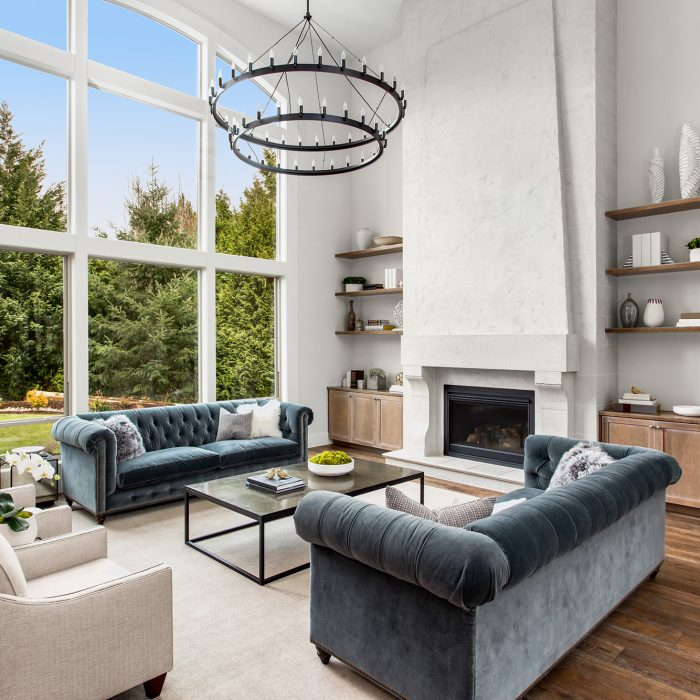 Beautiful living room in new luxury home with large bank of windows showing exterior view. ; Shutterstock ID 1339847978; PO: 575084731; Client: 9b556fe5-6314-453b-8028-861eb6f7a0e9