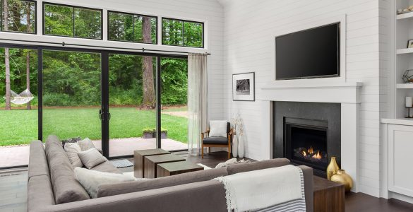 Living Room Interior with Fireplace and Hardwood Floors in New Farmhouse Style Home with Vaulted Ceilings. Shows View of Yard and Trees Through Sliding Glass Doors; Shutterstock ID 1253535817; PO: 575085641; Client: 9b556fe5-6314-453b-8028-861eb6f7a0e9